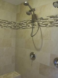 Huge shower, two shower heads and bench in master bath