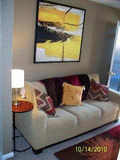 Full sized sofa with colorful  wall art.
