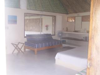 Palapa Mar bedroom showing corner of king bed and 1 of the 3 individual beds.