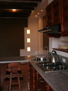 Beyond the kitchen is the living area with recessed lighting