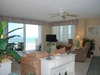 living room looking out towards balcony; that's the ocean you see through the windows