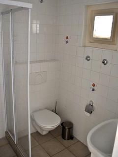 Badkamers met wastafel, wc en douche met warm water.