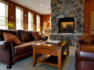 The dramatic common area boasts a double-sided fireplace. leather coaches and a flat screen tv.