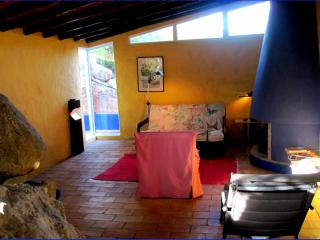 Casa das Rochas 1floor with integrated rocks and a chimney with a bed behind a rock ,see next foto