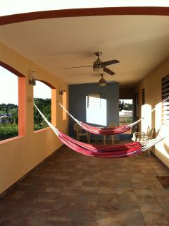 Enjoy sunset views in the outdoor space with hammocks, tables, chairs, lights, and ceiling fans