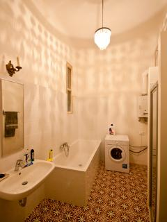 The bathroom has a washer-dryer and features Gothic tiles