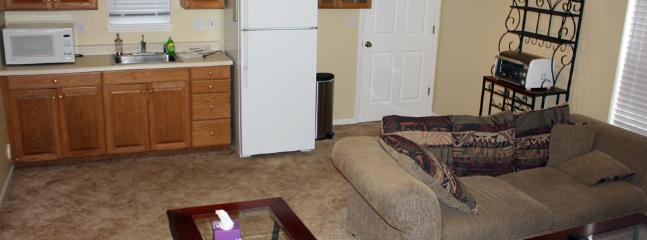 The living room/kitchenette area includes basic appliances and kitchen utensils.