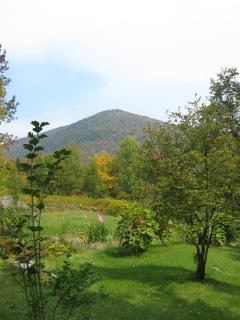 A nearby mountain, seen from the side of the yard and upper field..