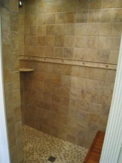 Large walk in shower, complete with teak bench