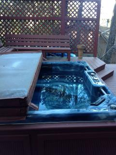 View of hot tub w/cover half opened