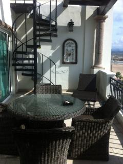Outdoor dining on lower deck off living area and master suite. Stairway to private rooftop deck!