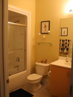 Guest bath features tub and shower surround enclosed with sliding glass doors.