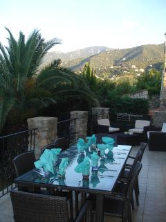 Al fresco dining on terrace overlooking garden and pool