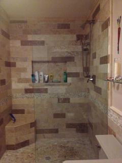 master bathroom-large walk-in shower with travertine tiles and river stone floor
