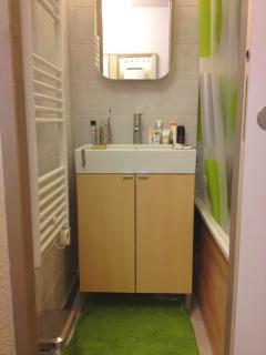 bathroom with large bathtube, wall drying racks, heater with racks