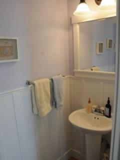 The first floor powder room is conveniently located and features a pedestal sink.