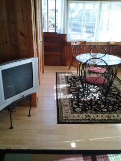 Oposite end of front room, table and chairs, extra TV.