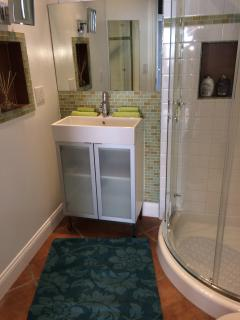bathroom with glass tiles, lighted make-up mirror, full length mirror