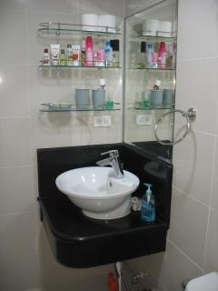 Bathroom: Sink, mirror and shelves; faucet w/ water heater