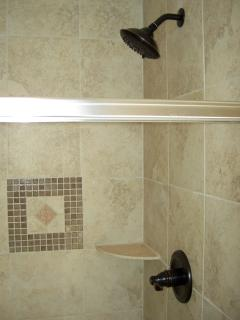 Master bathroom walk-in shower with oil rubbed bronze fixtures and ceramic tile