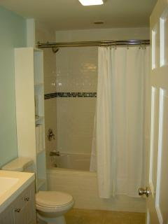 Full bathroom on main level with jet tub and ceramic tile. Shower over tub.