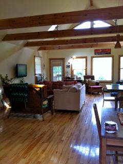 Great room w/ cathedral beamed ceilings,ceiling fans ,up lighting , mountain views door to deck/yard