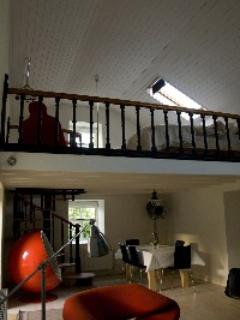 Dining area and upstairs bedroom on mezzanine level of Mulroe Studio