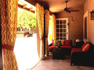 Covered patio with custom Sunbrella curtains and stylish lounge area with fan