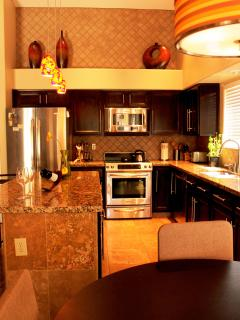 Granite countertop and travertine tiles throughout the kitchen