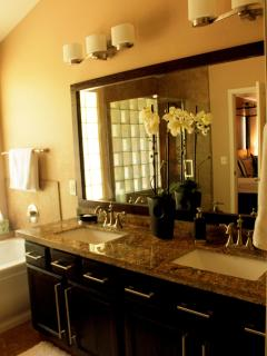 Double sinks in the master bathroom; designer lighting and mirror