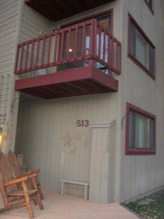 Entrance with 2 adirondack chairs and deck above off living room
