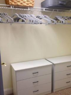 Walk in Closet with lots of hangers and storage and an ironing board