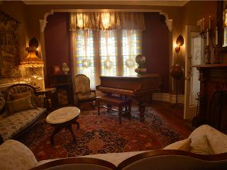 The Victorian Parlor with original fireplace and century old grand piano