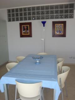 indoor dining area with a GLASS table and original Sicilian paintings