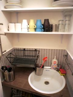 the small kitchen is fully equipped, refrigerator, stove, toaster, kettle and all the dishes
