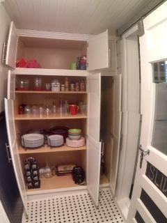 Pantry will all glasses, plates, blender, mixer, bowls, spices, oils,
