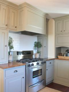 Beautiful kitchen with gas oven, dishwasher, refrigerator and small appliances.