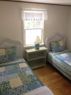 Second bedroom with twin beds and white wicker