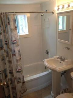 Newly renovated bath with tile floor and kohler fixtyres.