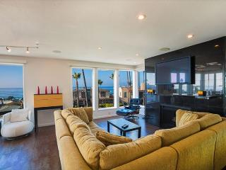 Living area has oversized couch, flat screen TV, fireplace and full ocean views