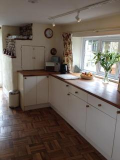 The kitchen is triple aspect, with french doors opening onto the attractive garden