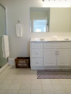 Bathroom with shower, 2 sinks, and laundry
