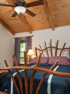 Locally Hand Crafted Sassafras Queen Bed under a vaulted ceiling with ceiling fan in one bedroom