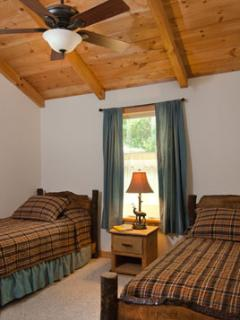 Two Rustic Twin Beds under a vaulted ceiling with ceiling fan in a second bedroom.