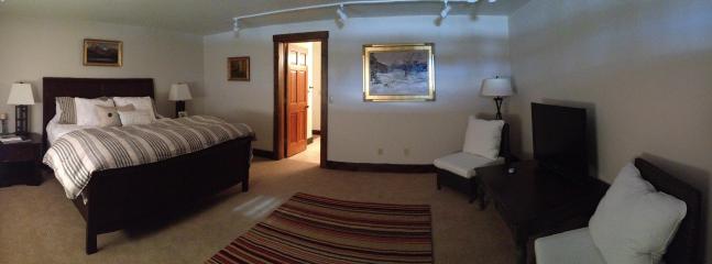 Quarto principal com cama king-size e área de estar