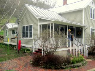 The farmhouse has three bedrooms, a front porch, a deck (not visible), and a patio.