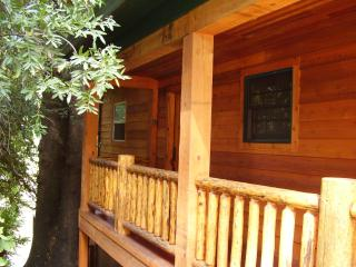 Cedar log railing on the front porch leads to the front door..