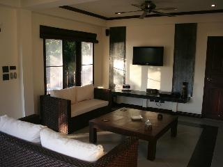 Apartment Lounge with wall mounted LCD TV and home cinema system.