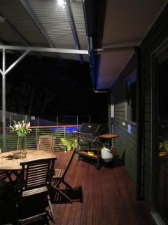 Back deck entertaining at night, looking to BBQ and pool