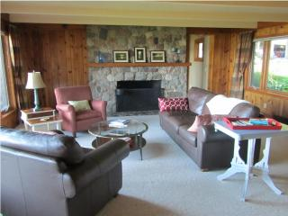 Living room with fieldstone fireplace - looks out on Lake Macatawa